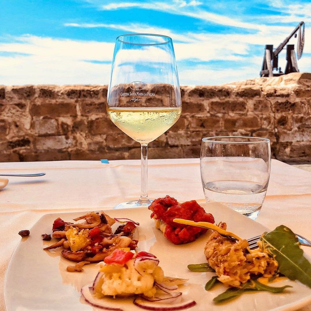 Bicchiere di vino, piatto di pesce, cielo e mare.